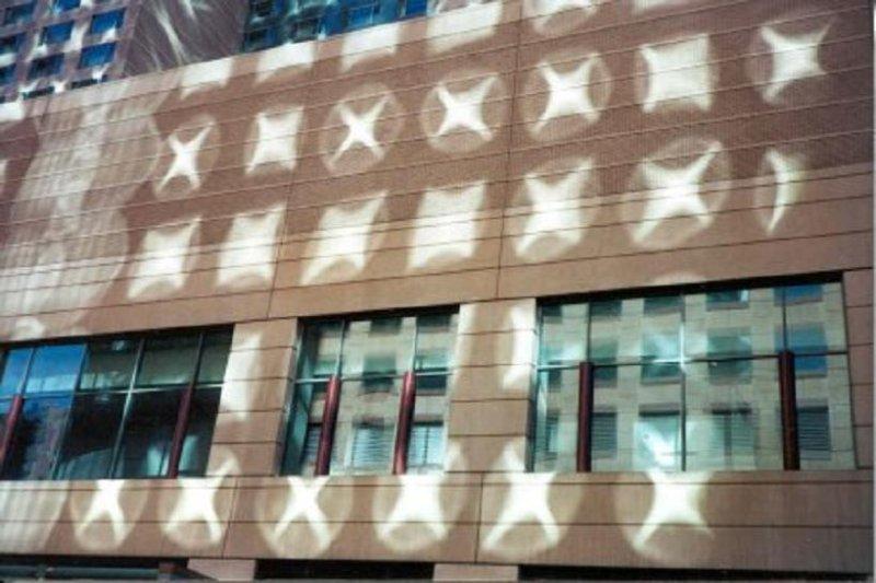 I cerchi di luce sulla facciata di un palazzo